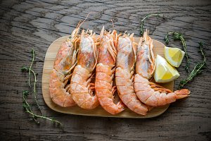 Raw shrimps with lemon wedges