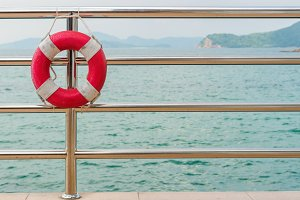 red Lifebuoy on railing by sea
