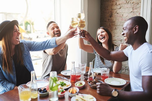 Group of four laughing adults toast…