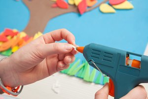 Child using a glue gun on a craft