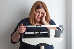 Woman crying on weight scale