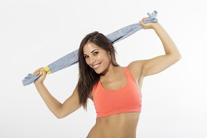 Studio portrait of beautiful girl dressed in fitness equipment
