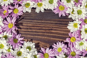 Crown of daisies on wooden background