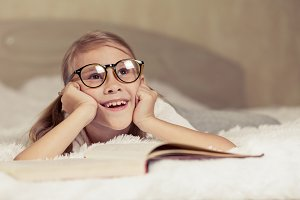 Happy little girl reading a book.