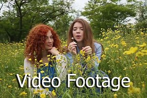 Girls blowing on dandelion