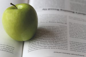 Open book with green apple