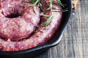 raw beef sausages on a cast-iron pan with rosemary and spices,  wooden table, selective focus