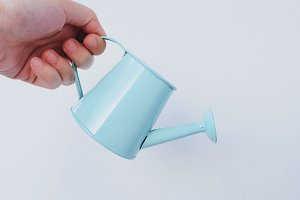 Hand holding little watering can