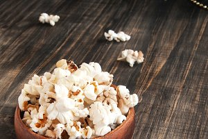 popcorn in a wooden plate on the background of Christmas trees