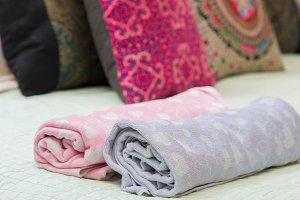colorful of towel roll on the bed.