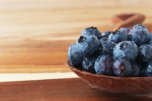 Big ripe blueberries on a wooden spoon, selective focus