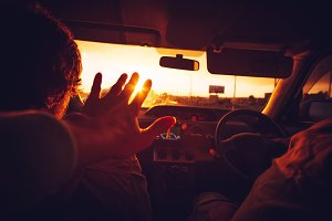 Hand touching sunset lights in a car
