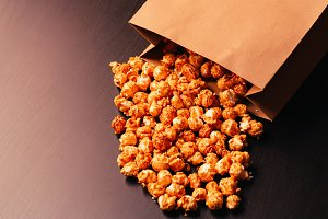 many popcorn in a paper bag on dark background