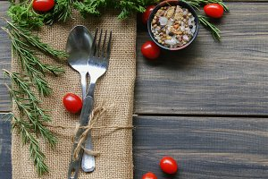 Table with cutlery, herbs, tomatoes and spices