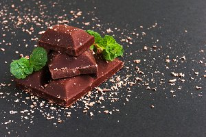 pieces of chocolate with mint lying on a wooden