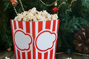 popcorn in the cup on background of Christmas trees and decorations