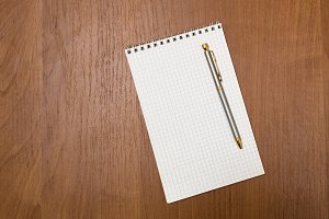 Pen rests on a notepad. Blank sheets