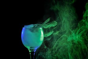 Blue and green smoke in a glass