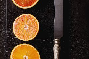 Set of Oranges on Marble with Knife