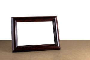 Old wooden photo frame on table