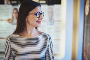 Young woman looking sideways in new eyeglasses