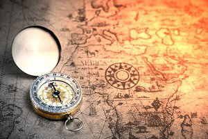 Retro compass on ancient world map