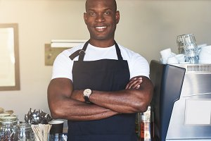 Handsome business owner stands by cafe counter