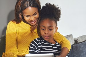 Little black girl and mom with tablet