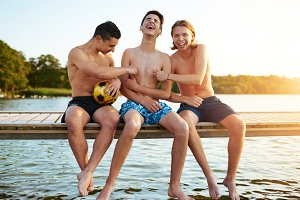 Two teenage friends tickling their mate