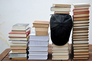 pile of books and black cap