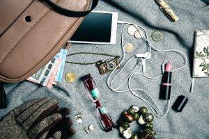 Feminine accessories from female handbag over grey background