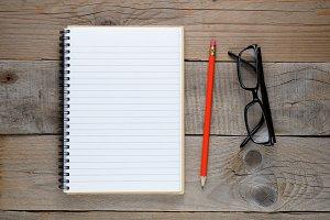 Notepad, pencil and glasses on table