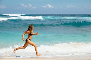 Woman running through sea water on a beach in Bali. Female runner jogging during outdoor workout on beach.