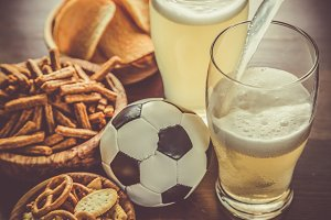 Pouring beer into glass with snacks and football