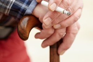 Hands with cigarette on cane
