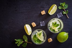Mojito and ingredients, dark stone background