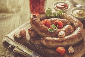 Grilled sausages served on wood board