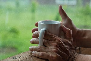 Male hands holding cup of coffee in the rainy day