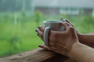 Female hands holding cup of coffee in the rainy day