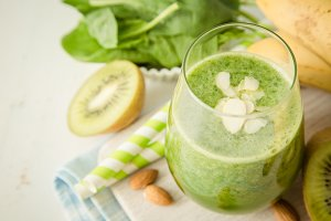 Green smoothie and ingredients on white background