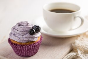 Blueberry cupcake on white wood background