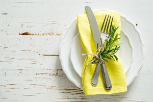 Spring table setting with rosemary and yellow napkin