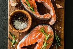 Raw salmon steaks on rustic background