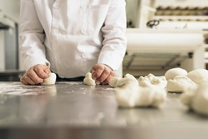 Baker kneading dough in a bakery.