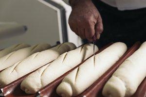 Baker kneading dough in a bakery.