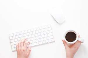 Girl on Keyboard Holding Coffee