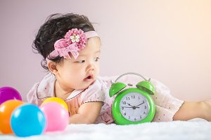 baby with a large alarm clock