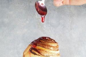 pouring the jam on cinnamon bun