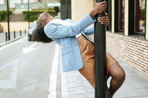 Woman dancing on street pole
