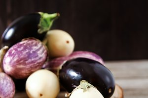 Fresh eggplants of different color on dark wooden background. Vegetarian food, health or cooking concept.